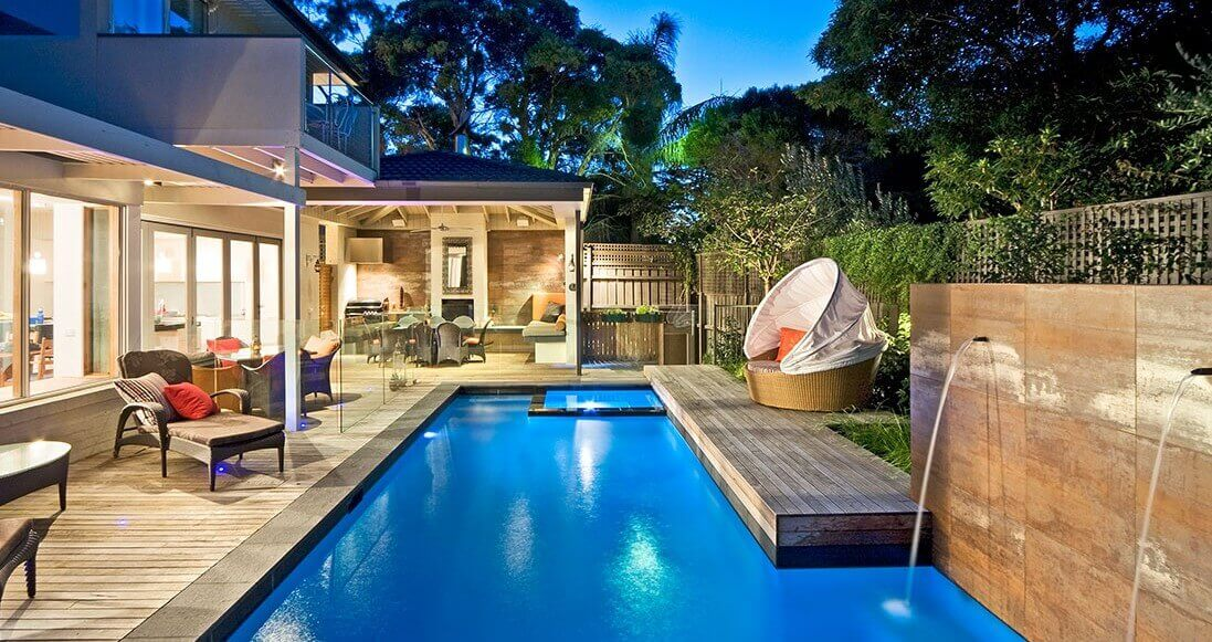 Natural Pools Concrete pool with a water feature and timber decking