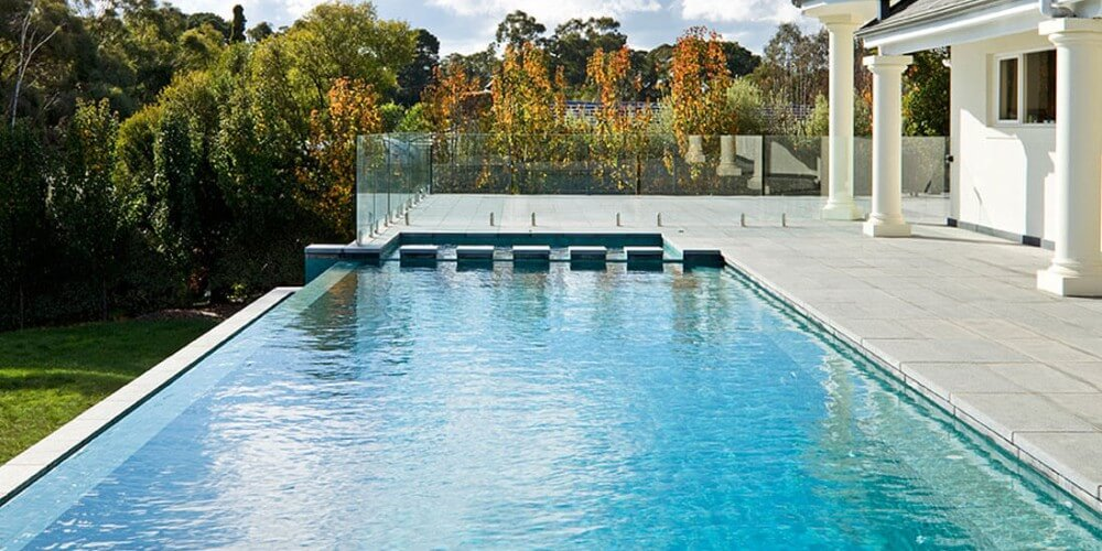Natural Pools Infinity Swimming Pool Installation with fence and tiling around the pool
